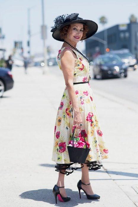 Mujer mayor usando un vestido de flores, sombrero y tacones