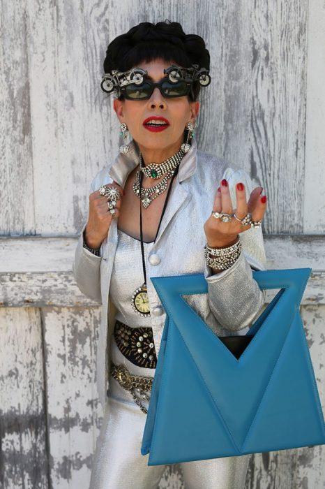 Mujer mayor usando un traje en color plata con una bolsa azul