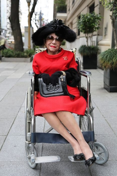 Mujer mayor en silla de ruedas usando un vestido rojo y una bolsa chanel
