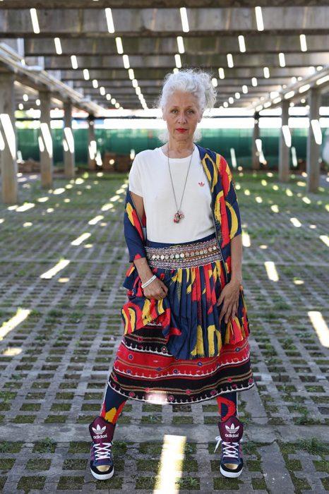 Mujer mayor usando un conjunto de falta y saco con estampado tribal y tenis nike