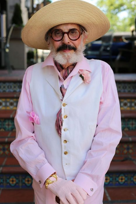 Hombre mayor usando una blusa color rosa y un chaleco en color blanco