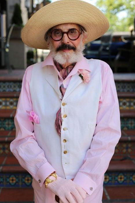 Hombre mayor usando una blusa color rosa y un chaleco en color blanco