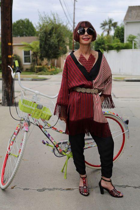Mujer mayor usando un conjunto rojo parada frente a una bicicleta