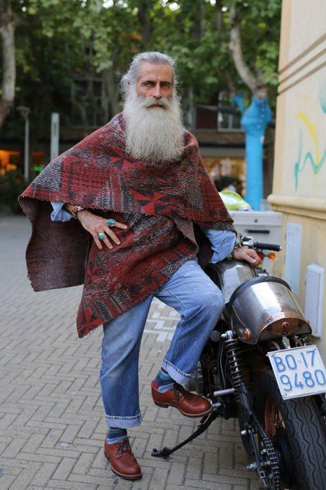 Hombre mayor con barba usando un poncho color rojo