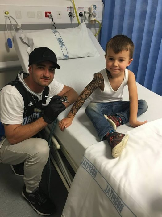Artista del tatuaje creando tatuajes temporales para niño en un hospital