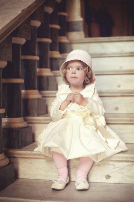 Pequeña elegante sentada en las escaleras