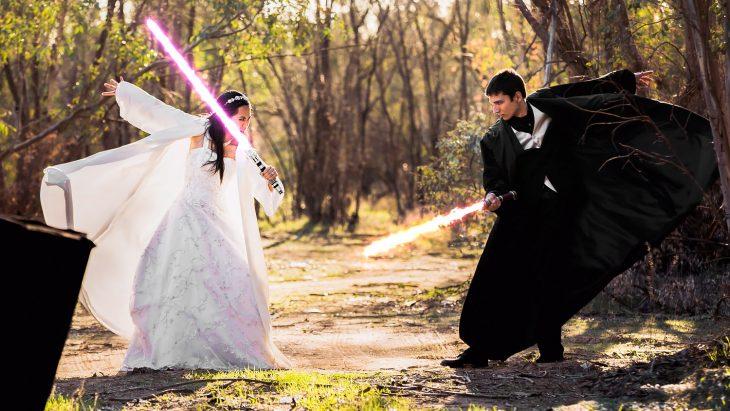 Pareja de novios peleando con sables de luz el día de su boda inspirada en Star Wars