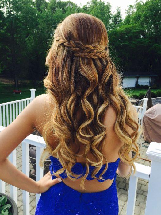 Chica con el cabello teñido en tonos cinnamon roll atado con una trenza en la mitad de la cabeza