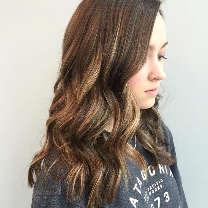 Chica con el cabello teñido en tono cinnamon roll en un corte long bob r