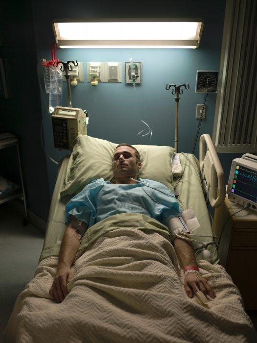 Hombre recostado en una cama de hospital