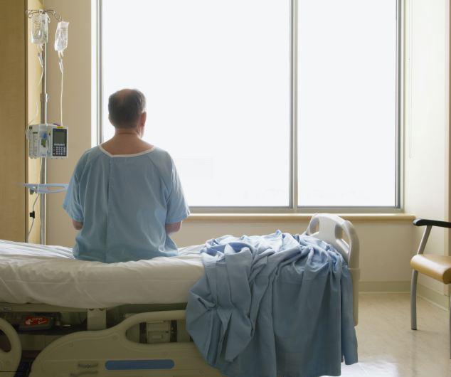 Hombre sentado en una cama de hospital observando una pared en blanco