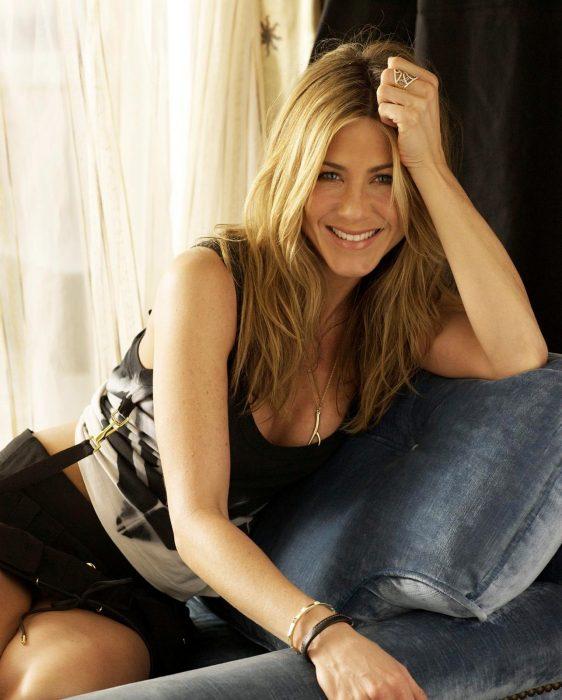 mujer rubia sentada con vestido y sonriendo