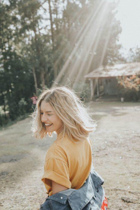 Personalidad de chica sagitario; mujer rubia de cabello corto riendo en la naturaleza