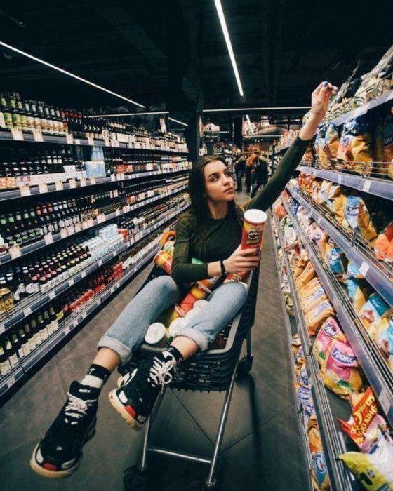 Personalidad de chica sagitario; mujer en carrito de compras en supermercado