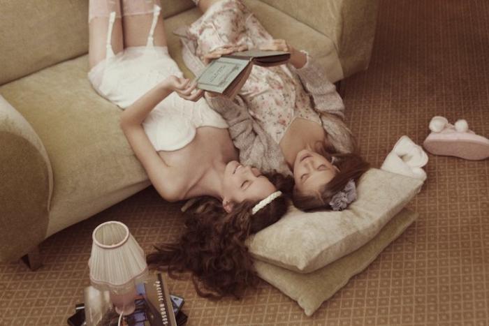 Chicas recostadas sobre el suelo leyendo un libro