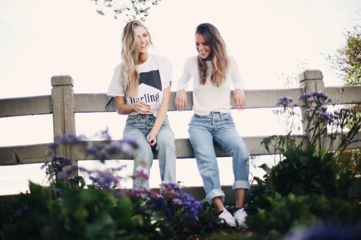 Chicas sentadas en una cerca conversando y riendo