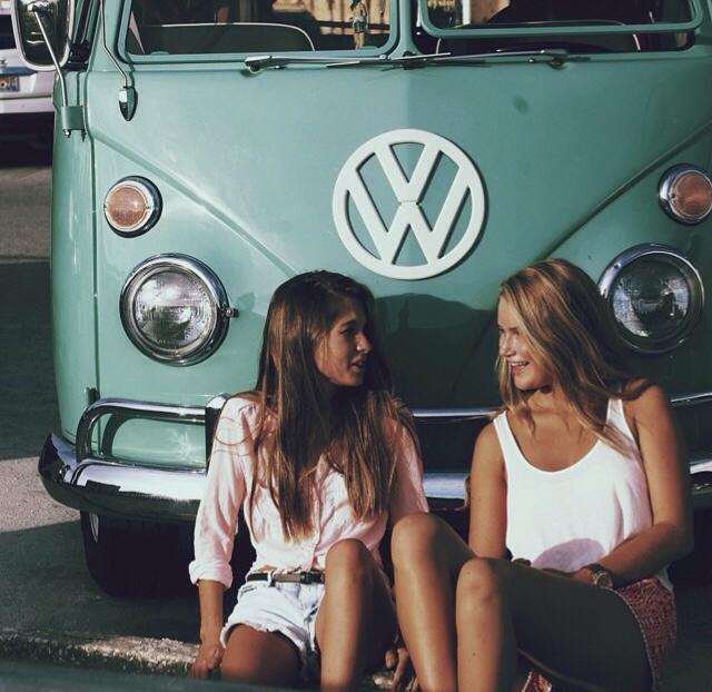 Chicas recargadas sobre la parte frontal de una camioneta conversando
