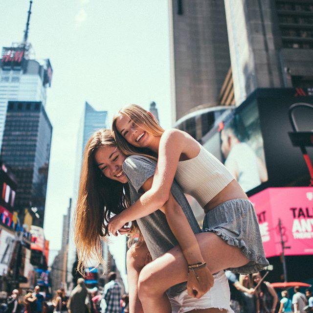 Chica en la espalda de otra disfrutando de la ciudad mientras ríen