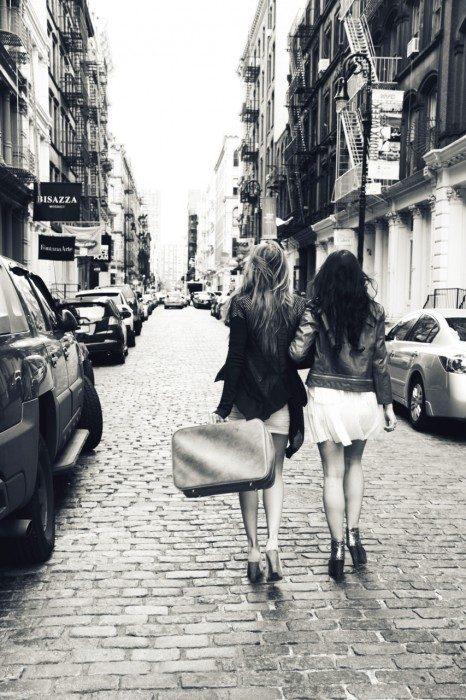 Chicas sujetando una maleta mientras caminan por la calle