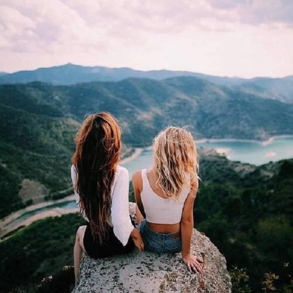 Chicas sentadas en una piedra mientras miran las montañas