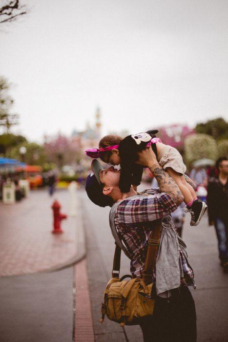 Padre besando a su hija mientras pasean por Disney