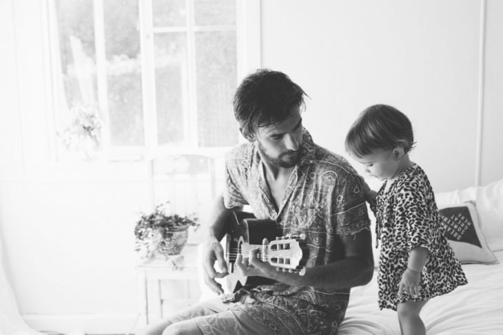 Padre tocando la guitarra para su hija