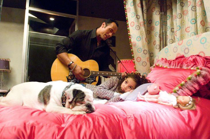 Escena de la película entrenando a papá. Papá tocando la guitarra para su hija