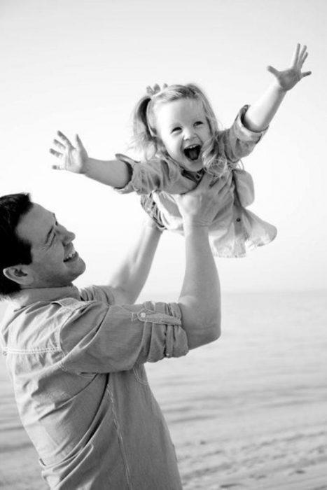 Padre jugando con su hija en la playa