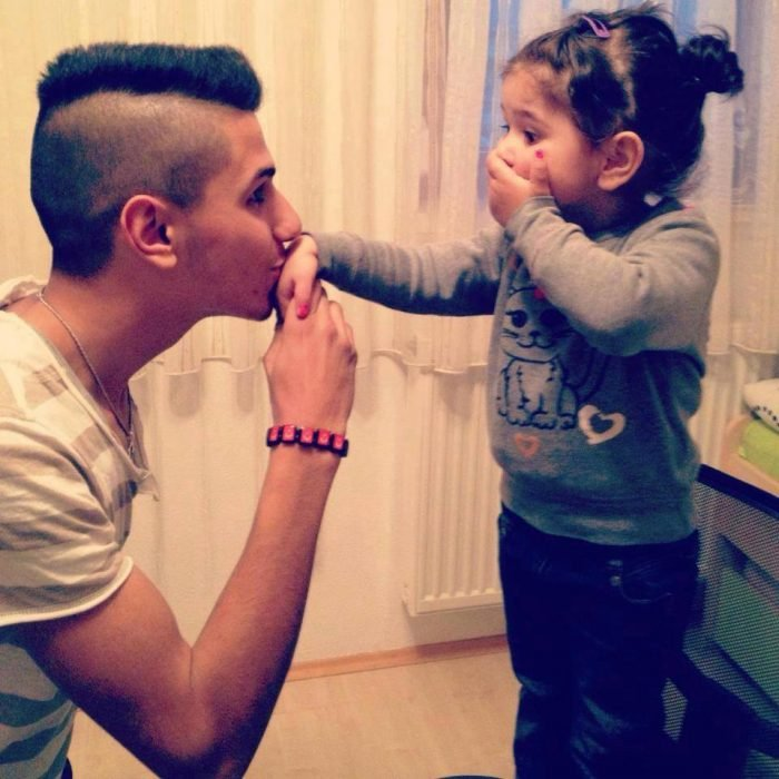 Chico besando la mano de su hija