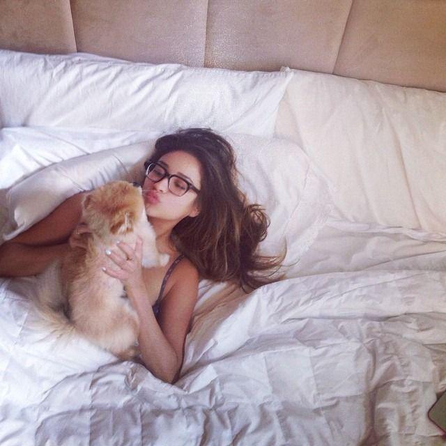 Chica en la cama despertando con su perrito