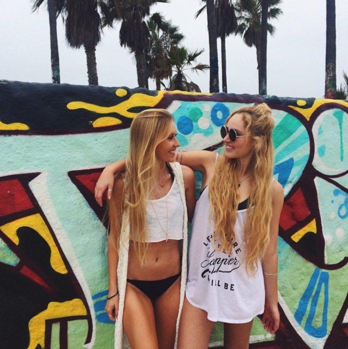 Chicas abrazadas recargadas en una pared de la playa