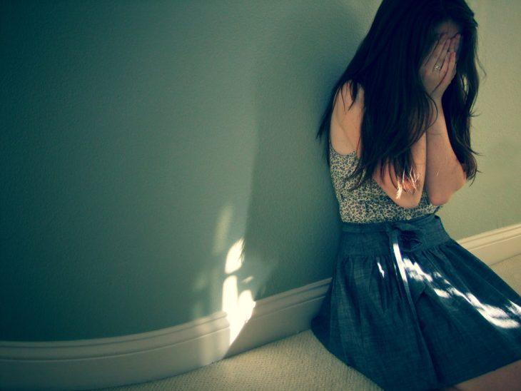chica sentada en el suelo llorando