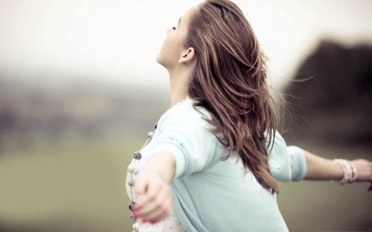 chica abriendo los brazos en el campo