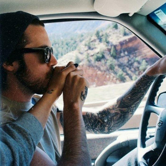 chico tatuado conduciendo besa la mano de chica