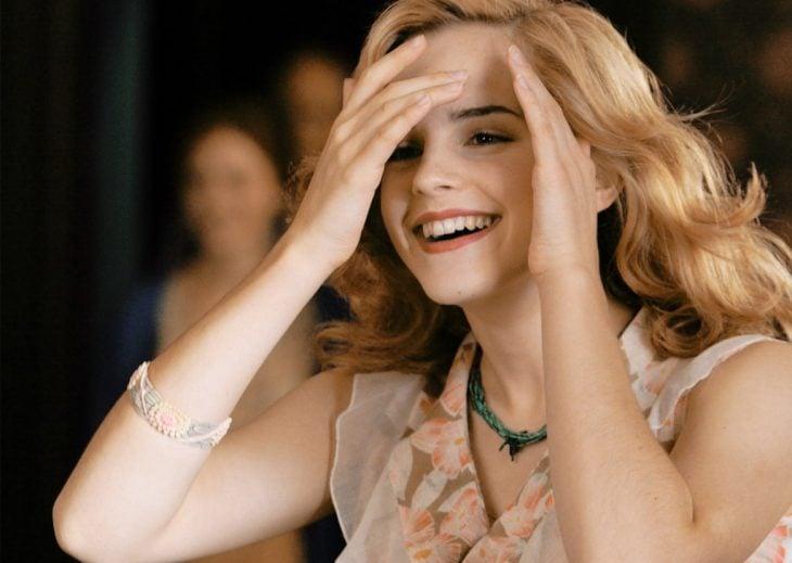 mujer rubia con manos en la cara sonriendo