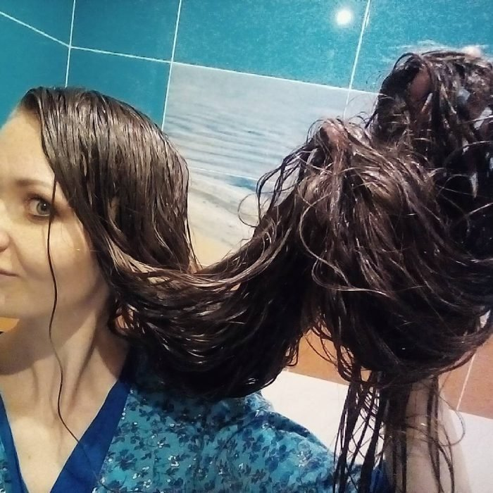 Chica mostrando su cabello trenzado luego de tomar una ducha
