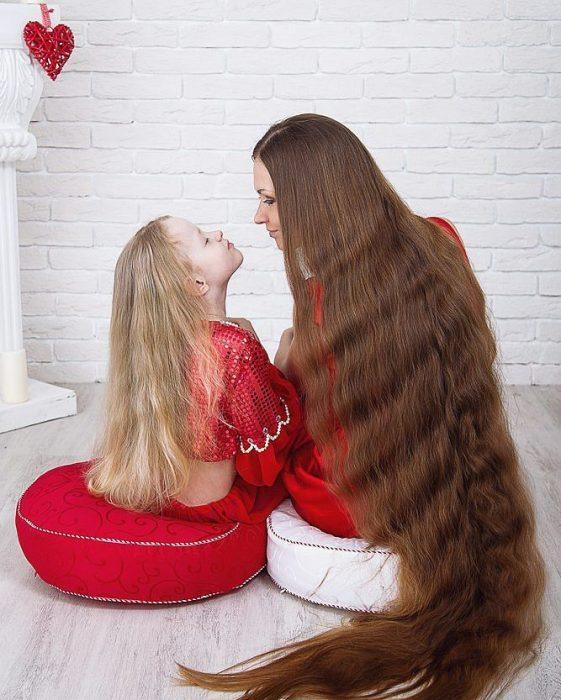 Madre e hija con el cabello largo hasta los tobillos mirándose de frente