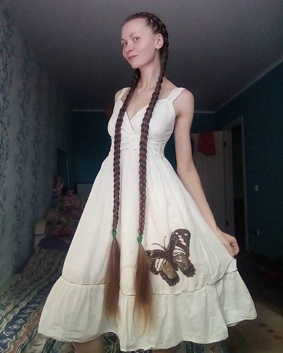 Chica luciendo su cabello largo hasta los tobillos trenzado en dos trenzas