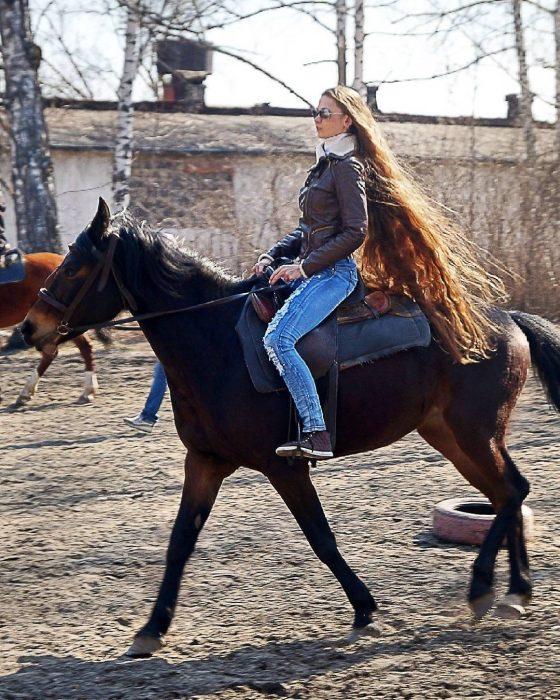 Chica con el cabello hasta los tobillos paseando en caballo