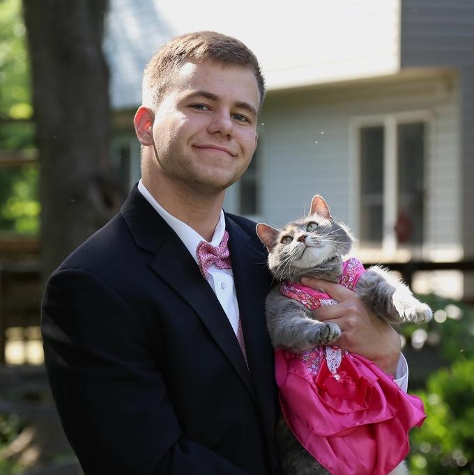 Chico que llevó a su gato al baile de graduación sosteniéndolo mientras el gato usa un vestido rosa