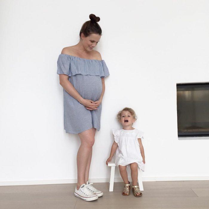 Chica embarazada de 40 semanas parada junto a su primer hijo