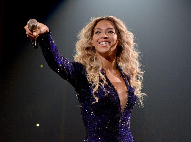 mujer morena sonriendo con microfono en la mano
