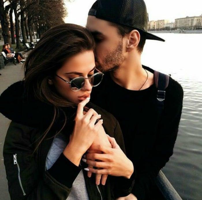 pareja abrazanda al lado de un lago