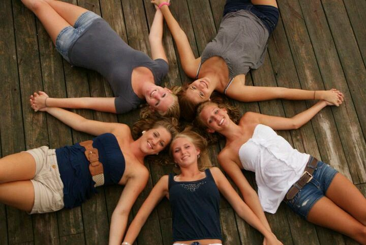 Chicas recostadas en el suelo formando una estrella con sus brazos
