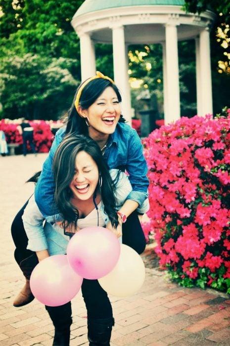 Chica sobre la espalda de otra mientras sujetan unos globos