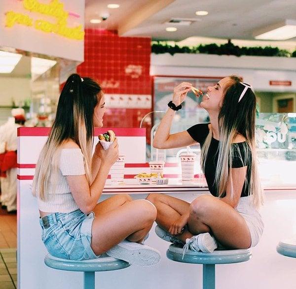 Chicas sentadas en su restaurante favorito comiendo hamburguesas
