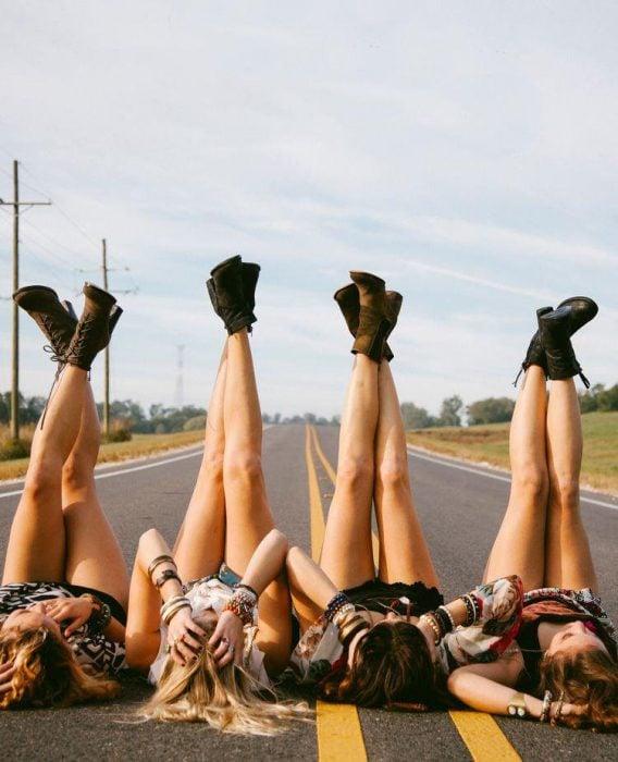 Chicas recostadas en la carretera con los pies arriba