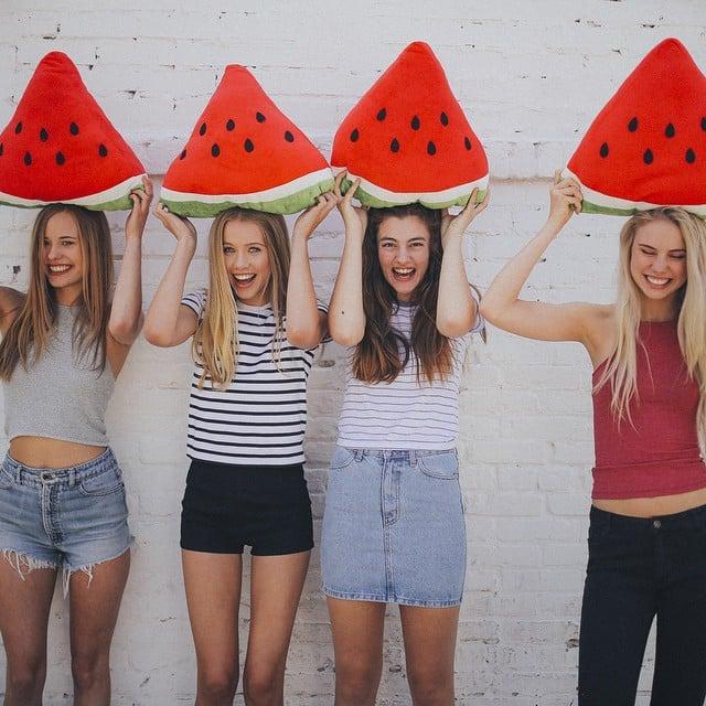 Chicas sosteniendo rebanadas de sandia sobre sus cabezas