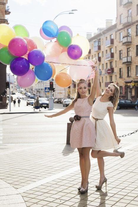 Chicas paradas en medio de la calle sosteniendo unos globos
