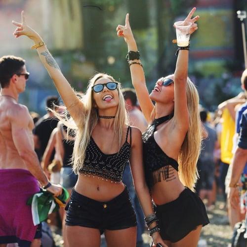 Chicas levantando los brazos durante el festival de coachella
